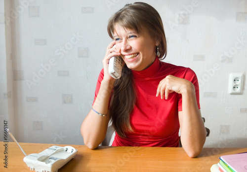 The girl laughs speaking by phone