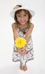 A happy, smiling girl holds a yellow flower
