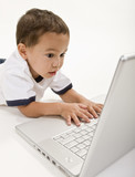 A young boy playing on a laptop