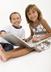 Two young kids playing on a laptop computer
