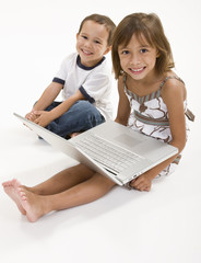 Two young kids playing on a laptop