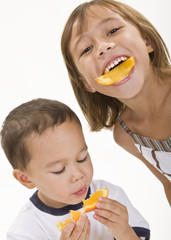 Two young children enjoying orange peel slices