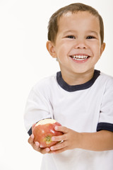 A young boy holds a fresh red apple