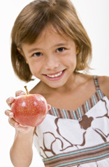 A young girl holds a fresh red apple