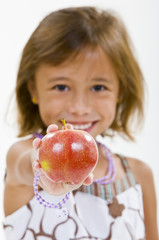 A young girl holds a red apple.