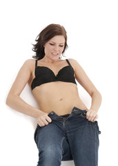 beautiful brunette woman struggling to get into tight jeans