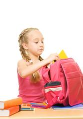 Little schoolgirl packing her rucksack ....