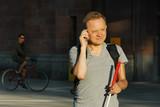 Fototapety Blinder Mann telefoniert unterwegs