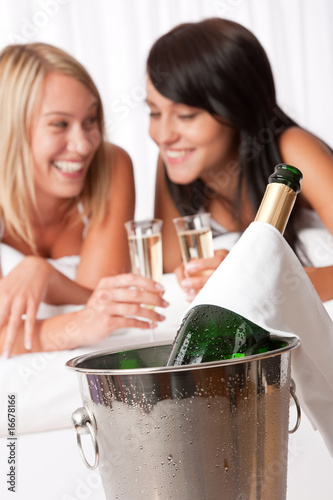 Two young women toasting with champagne