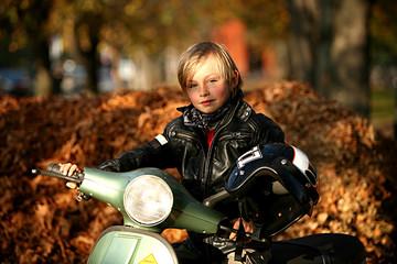 Junge auf Vespa im Herbst