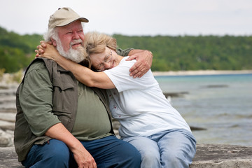Senior couple sitting at shores edge