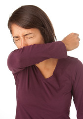 Woman Coughing into Elbow