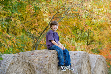Boy Sitting on Hay Bales in the Fall