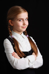 Girl in school uniform on black background; looking at a camera