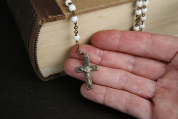 Hand mit Rosenkranz und Bibel