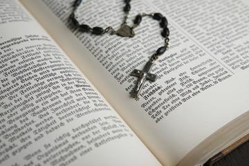 Buch aufgeschlagen mit Rosenkranz