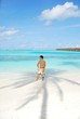 Young man standing on a tropical beach in Maldives