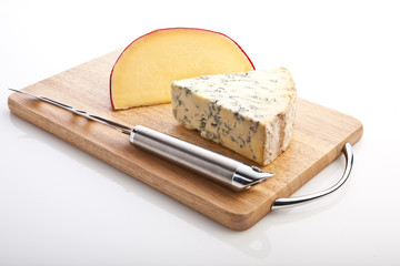 Segments of Brie and Stilton  with a knife on a board