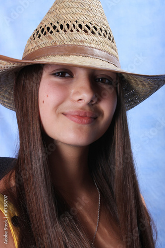 A studio portrait of girl is in a cow-boy hat.