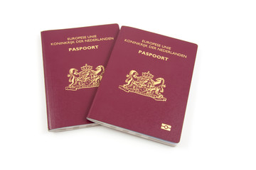 Two Dutch passport over white background