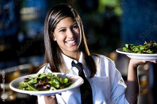 Leinwandbild Motiv Hispanic waitress serving two plates of salad in a restaurant