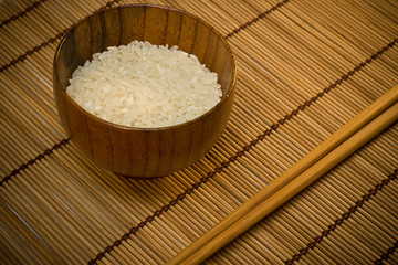 white rice in bowl on wooden mat