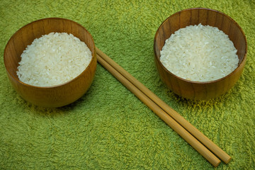 bowls with rice and sticks on green mat