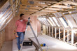 Electrician leaning against ladder in attic under construction