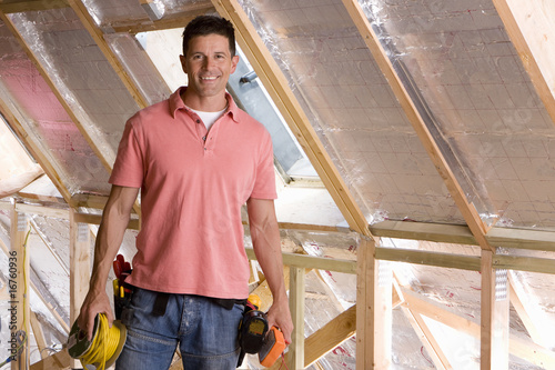 Smiling electrician standing in attic under construction