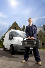 Handyman in coveralls holding toolbox near work van