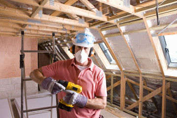Construction worker wearing protective mask and holding drill in attic