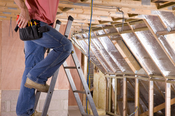 Electrician working on ladder in attic under construction
