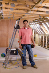 Electrician standing in attic under construction