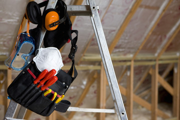 Tool belt, goggles, mask and ear protectors hanging from ladder