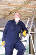 Man in coveralls on ladder looking up at ceiling insulation