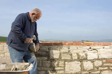Stonemason chipping at stone with mallet next to wall