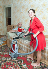 Woman running the vacuum cleaner against her husband