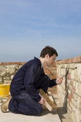 Man bricklaying wall with trowel