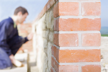 Close up of brick wall with bricklayer in background