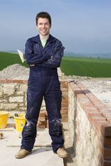 Smiling bricklayer standing next to brick wall