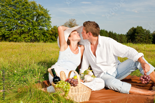 Young man and woman kissing while having picnic