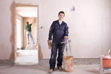 Smiling man mixing plaster in house under construction