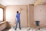 Man plastering wall in house under construction