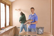 Men plastering wall in house
