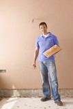 Man holding towel near plastered wall