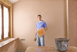 Man holding trowel next to plastered wall
