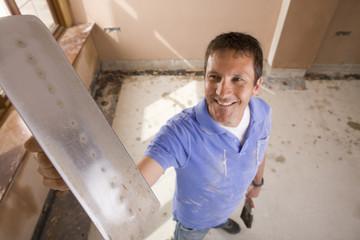 Smiling man holding plastering trowel