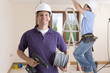 Smiling electrician holding cable spool and drill with co-worker wiring ceiling in background