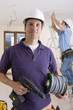 Electrician holding cable spool and drill with co-worker wiring ceiling in background