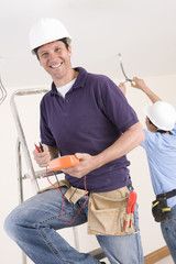 Smiling electrician holding voltmeter on ladder with co-worker wiring ceiling in background